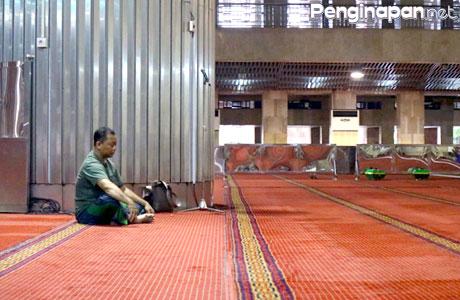 Seorang pengunjung duduk di dalam Masjid Istiqlal
