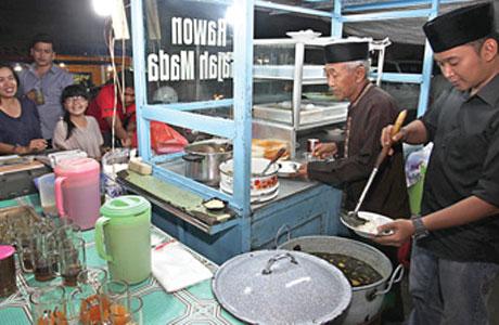Dimas sedang melayani pembeli rawon di warungnya di Jalan Gajah Mada.